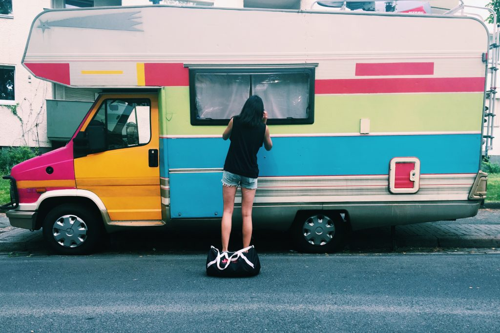 A woman in shorts peering through a window of an multi-colored rainbow RV.