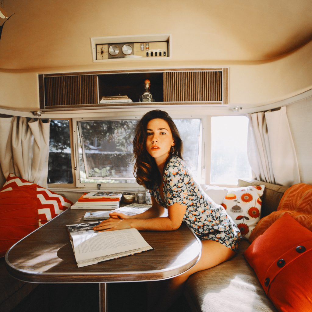 A woman reading in an RV with orange and red pillows with a large window behind her.