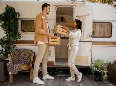 Man and woman handing provisions to one another in front of an RV.