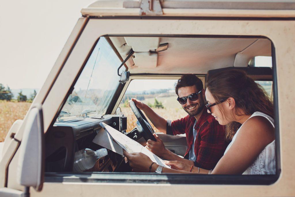 A man driving an RV while a woman shows him a map.