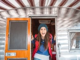 A happy woman poking her head out of a camper.