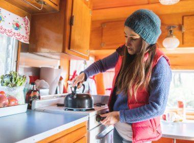 Woman preparing tea in her camper.