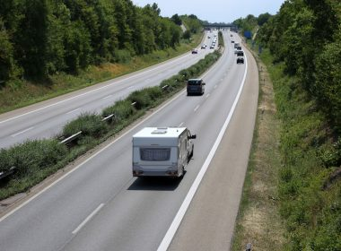 Vehicle towing camper in the slow lane on the highway.