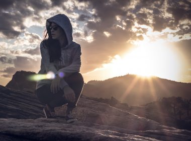 Hooded woman kneeling in the desert looking around as the sun starts to set.
