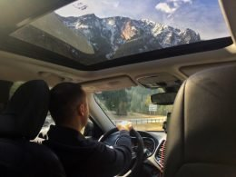 A man drives his tow vehicle through the mountains which can be seen towering above through the sun roof.